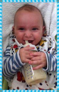 Baby lacht mit Flasche